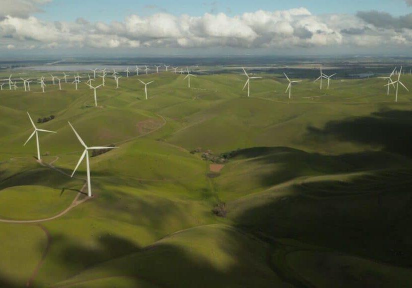 wind turbine farm in green rolling hills